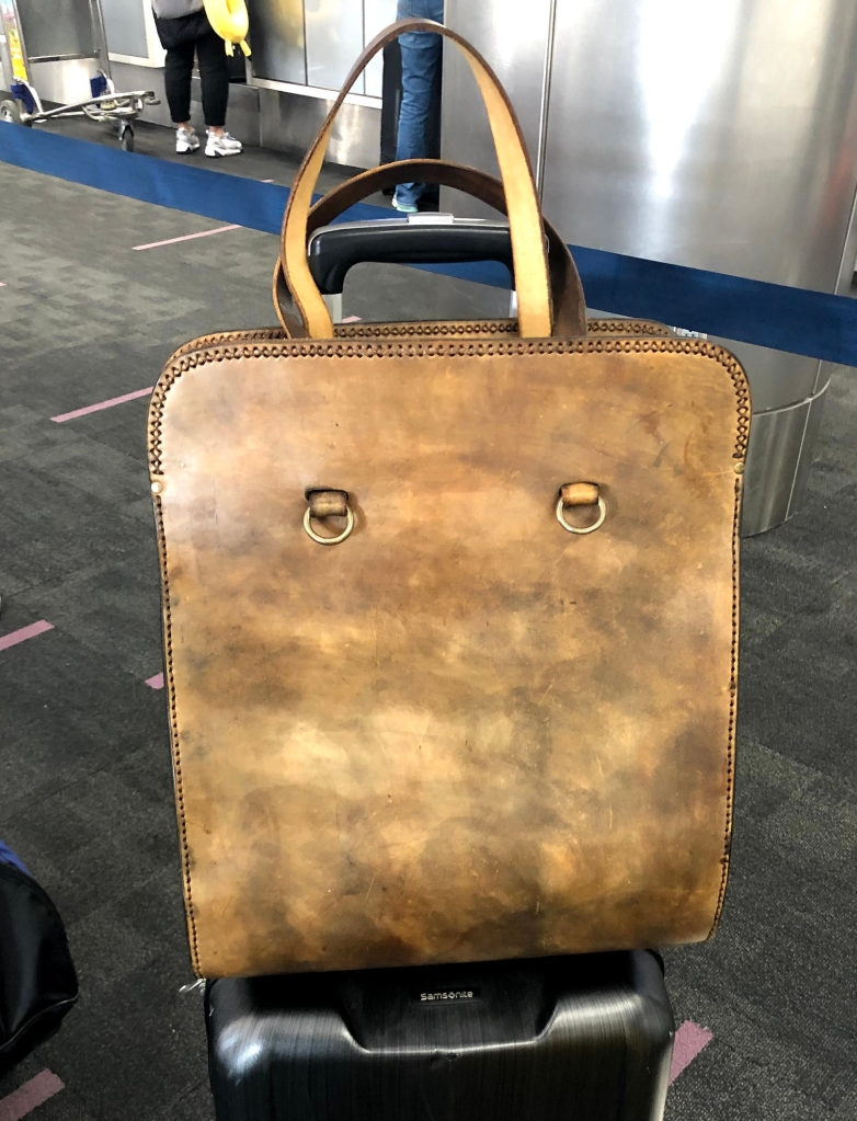 Photo of a stiff leather carry on bag.